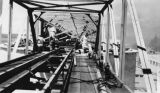 Conveyor on top of chip bins with woman posing during the construction of the Bloedel, Stewart and...