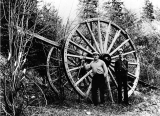 Logger with felling ax in front of big wheels, probably Pacific Northwest, n.d.