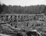 Men walking on long curved trestle, unidentified Bloedel-Donovan lumber operation
