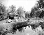 Family relaxing by river near farmhouse, Yakima Valley, ca. 1910s
