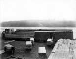 Loading lumber onto railroad cars on barge, Puget Mill Co., Port Ludlow, Washington, December 1918