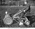 Push tractor with rear-end seat and disc tiller implement being demonstrated in field, ca. 1952