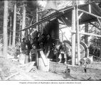 Logging crew posing in front of donkey engine, ca. 1903