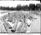 Men working on log boom, ca. 1903