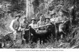 Group of men posing with guns and carcass of a bear tied to a pole, vicinity of Clatsop, Oregon,...