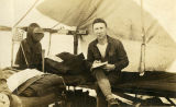 Soldier seated on a cot inside a tent, vicinity of Clatsop, Oregon, July 1918