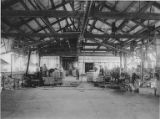 Interior view of canning room with men sealing cans and moving carts, Los Angeles Tuna Canning...