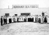 Group of workers standing outside a processing building, Normandy Sea Food Co., San Diego,...