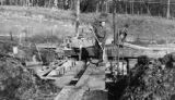 Man with shovel walking on planks, construction of the Bloedel, Stewart and Welch kraft pulp mill...