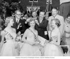 "Senator Henry M. Jackson placing a crown on woman with ""Norway"" sash at the 17th of May..."
