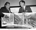 Senators Henry M. Jackson and Warren G. Magnuson displaying photographs for the Youth Conservation...