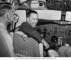 Senator Henry M. Jackson sitting in the cockpit of a flight simulator with unidentified man during...