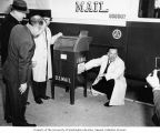 Senator Henry M. Jackson placing a sticker on a U.S. Mail box while others watch, probably in...