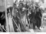 Senator Henry M. Jackson holding a shovel while standing with a group of people at a...