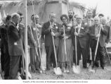 Senator Henry M. Jackson holding a shovel in a group of people during a prayer prior to a...