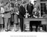 President Lyndon B. Johnson handing a pen to Senator Henry M. Jackson after signing a bill...