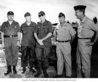 Senator Henry M. Jackson in military fatigues talking with soldiers on an air field, Bien Hoa Air...