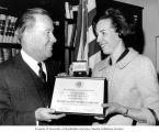 Senator Henry M. Jackson presenting a framed certificate to Senate staff member Rosemary Donnelley...