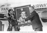 Senator Henry M. Jackson accepting a painting of himself portrayed as a clown at a party thrown in...