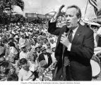Senator Henry M. Jackson delivering a speech outdoors to a crowd of senior citizens holding...
