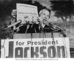 Senator Henry M. Jackson standing behind a podium and holding up a copy of the Boston Herald...