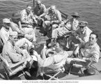Congressman Henry M. Jackson and U.S. Congressional delegation sitting around the prow of a boat...