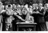 Senator Henry M. Jackson, center, and others watching President Jimmy Carter sign a bill...