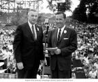 Senator Henry M. Jackson standing with an unidentified man at a microphone in front of a crowd at...