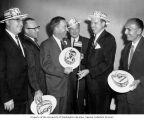 Senator Henry M. Jackson posing with Mike McCullion and others wearing McCullion campaign top hats...