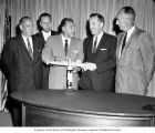 Senators Henry M. Jackson and Warren G. Magnuson standing behind table with others and holding a...