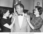 "Representative Henry M. Jackson standing in his office while two unidentified women pin ""S.W...."
