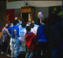 Schoolchildren clustered around Rabbi Norman Hirsh who is reading from Torah, Temple Beth Am...