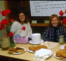 Two young women at desk with red flowers and plates of cookies, Temple Beth Am religious school,...