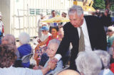Mayor Paul Schell shaking hands with Bernice Wolf in audience at the groundbreaking for The...