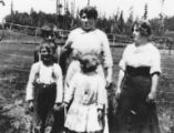 David Coe's family (two women and three children) in front of fenced pasture, Longbranch