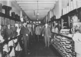 Five men inside Friedman & Wolfson Menswear store at First Ave. and Columbia St., Seattle, ca....