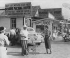 Edith Braun handing or accepting papers from a man in front of fruit stand, ca. 1952