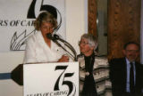 "Carolyn Danz at podium with another woman and Joshua Gortler at ""75 Years of Caring,""..."