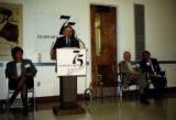 "Joshua Gortler at podium with others sitting nearby at the ""75 Years of Caring,"" the..."