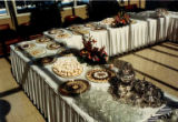 White cloth-draped tables covered in trays of pastries along with floral arrangements and silver...