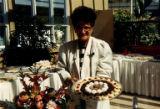 Caterer holding tray of pastries for 75th anniversary of Carolyn Kline-Galland Home, 1989