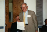"Harold Seligman holding document at ""75 Years of Caring,"" the 75th anniversary..."