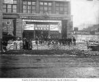 Men with piles of goods in front of the Cooper & Levy Pioneer Outfitters store, Seattle, ca....