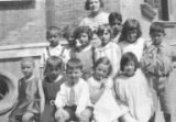 Group portrait of kindergarten class and a woman in front of a building, probably the Tientsin...