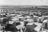 Rows of small buildings, probably housing, made of corrugated metal, Israel, ca. 1957