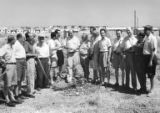 Tour group standing in field with houses in the background, Israel, ca. 1957