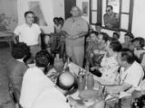 Group seated around table listening to man speak, Israel, ca. 1957
