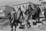 Children walking down concrete steps with houses in background, Israel, n.d.