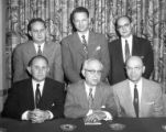 Six men at table with Seymour Kaplan in back row, middle, n.d.