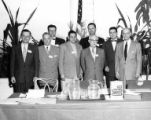 Group photo of eight men at table with copy of The Trouble-Makers: An Anti-Defamation League...
